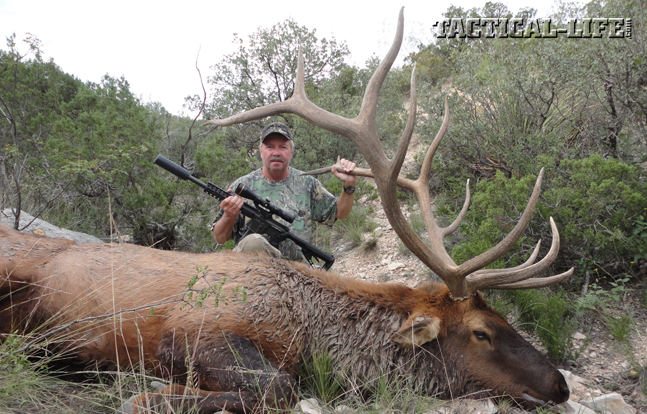 Bill Wilson, owner and founder of Wilson Combat, kneels behind his giant 6x6 trophy bull.