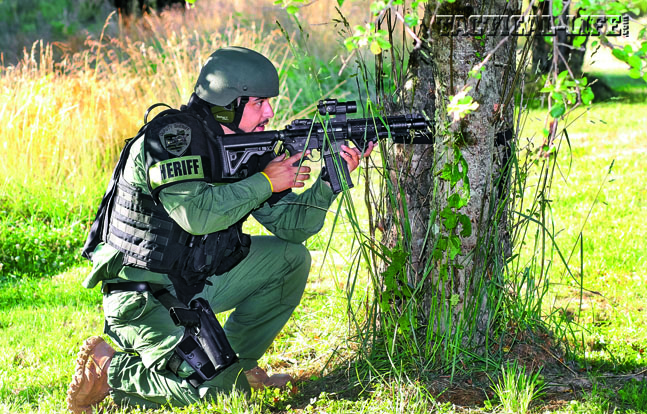 An ACSO SRT deputy takes a position behind a tree as he covers the perimeter with an AR-platform rifle during a training exercise.