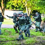 Members of the Athens County Sheriff's Office Special Response Team practice moving into position before performing an entry into an occupied structure during training.