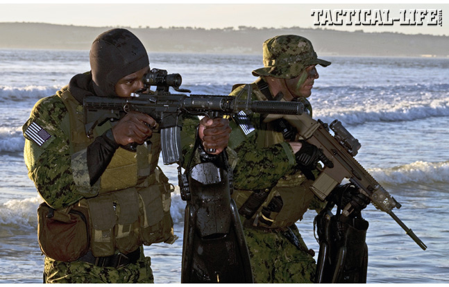 Two Navy SEALs come ashore armed and ready for action. SEALs carry a number of rifles, including the M4A1 (front) and the FN SCAR MK 17 (rear).
