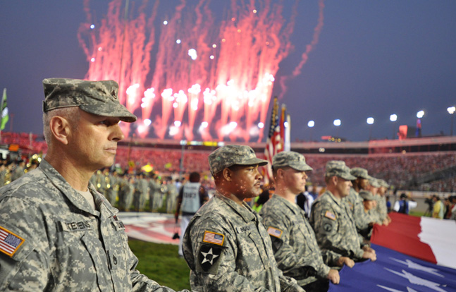 U.S. soldiers and airmen with the Virginia National Guard unfurl a giant American flag during the playing of the national anthem prior to the Wonderful Pistachios 400 NASCAR Sprint Cup Series race in Richmond, Virginia.