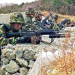 During a training exercise, ROK Marines armed with K2 rifles assume a covered position.