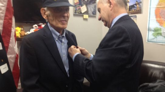 U.S. Sen. Jack Reed presents 92-year-old Navy vet Frank Poli with medals he earned after serving in World War II