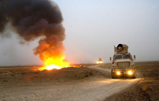 A blast near a convoy shows the devastating potential of IEDs in the field. Increasingly, the U.S. armed forces have used up-armored trucks and MRAP vehicles for what used to be routine transport missions.