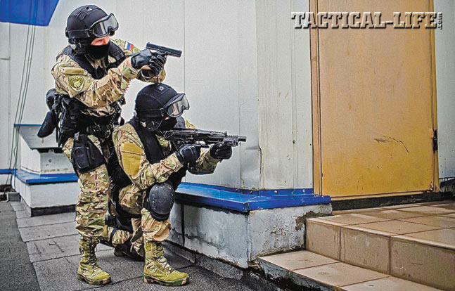Two OMOH operators prepared for entry. They are armed with a Glock pistol and what appears to be an SR-2 submachine gun.