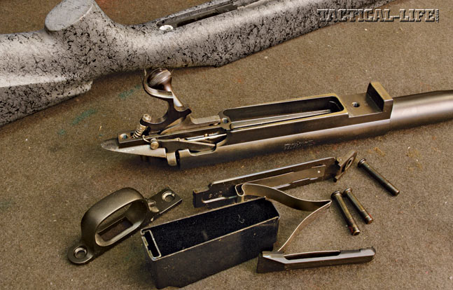 DISASSEMBLE: Remove the bolt from the gun, and make sure the gun is empty of all ammo. Now remove the stock from the gun using a screwdriver that correctly fits the slot. Remove the magazine box from the action. Using a punch that is the correct size for the pins, remove the front and rear trigger retaining pins. Note that they are removed in opposite directions.