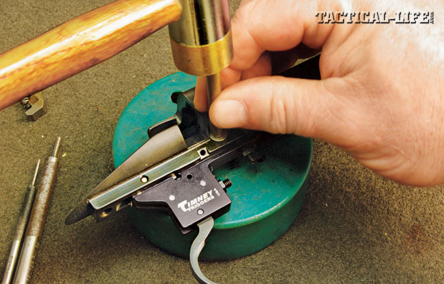 IN WITH THE NEW: Slide the new trigger into place, pushing back on the bolt stop spring and stretching it enough that the trigger can be inserted and the rear pin pushed into place to hold it. Back out the screw on top of the front of the trigger. Now, push the front of the trigger into place and insert the front retaining pin. Tap the front retaining pin into place with a brass punch.