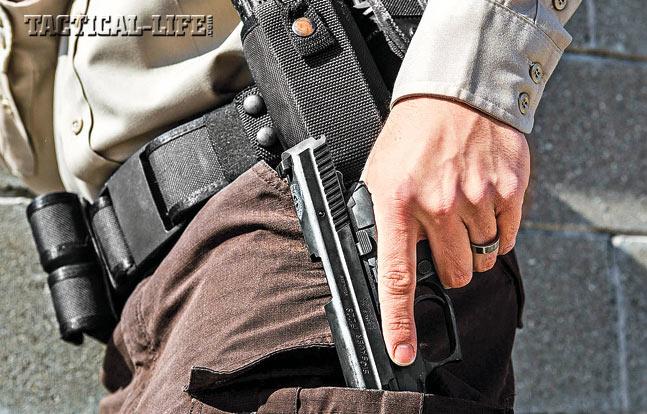 Step 2. With the magazine cleared from the pistol, now move to stow the handgun in an accessible support-side pocket to facilitate a reload.