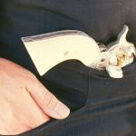 Without a belt and holster, a Colt Peacemaker tucked in waistband.