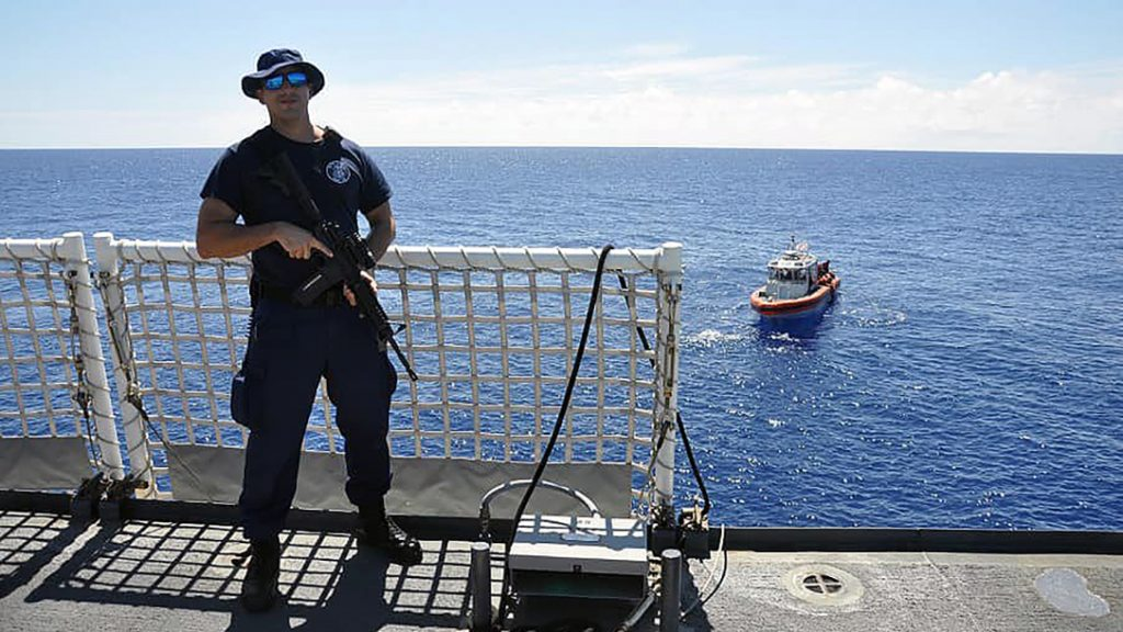 A Coast Guard crewman used well-placed rifle fire to turn away a shark.