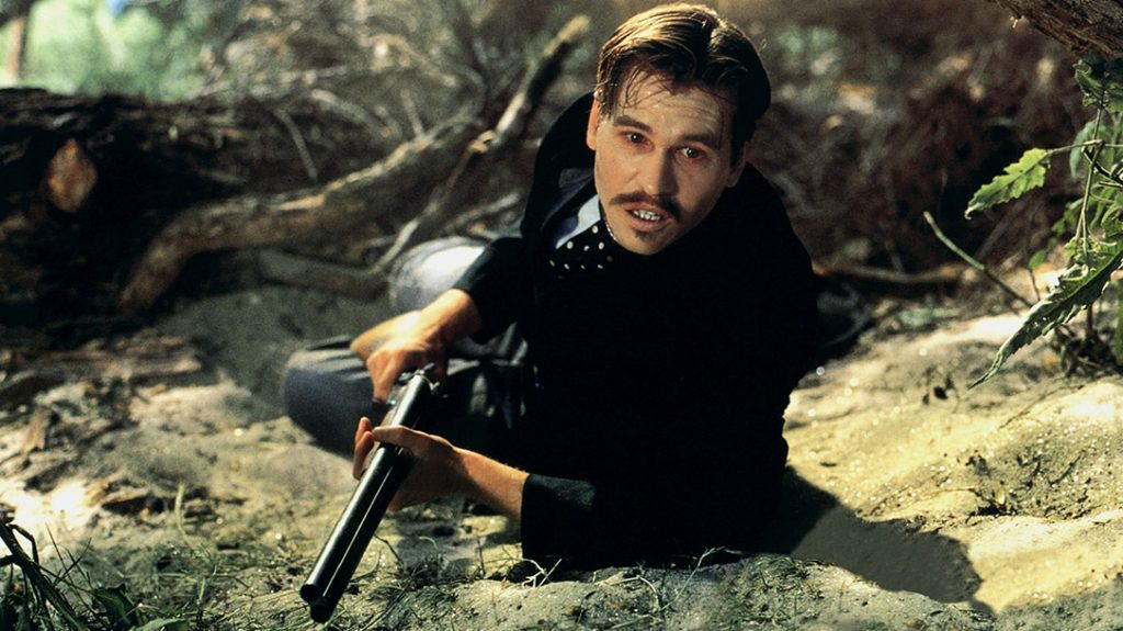 Val Kilmer wields a coach gun as Doc Holiday in arguably one of the best Wyatt Earp movies, Tombstone (1993).