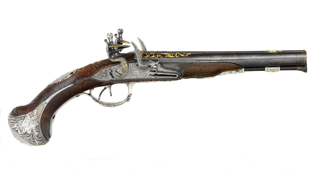 Flintlock pistols with side-by-side barrels became popular in England and France in the second half of the 18th century. This luxuriously decorated French pistol exhibits the fashionable Rococo taste for asymmetry and whimsy in its elaborate parcel-gilt silver mounts and silver-wire inlay. (Metropolitan Museum of Art)