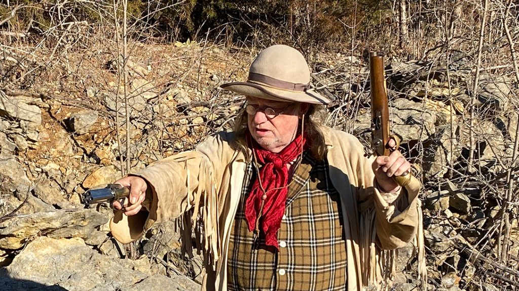 The author wielding both the pepperbox pistol and a single-shot pistol.